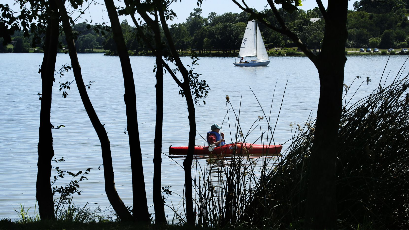 A kayaker and sailboat take to the water at White Rock Lake in Dallas, Wednesday, May 27,  2020. (Tom Fox/The Dallas Morning News)