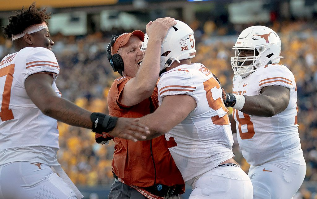 Texas lineman Samuel Cosmi (52) celebrates a touchdown with offensive line coach Herb Hand, center left, during an NCAA football game against West Virginia, Saturday, Oct. 5, 2019, in Morgantown, W. Va.
