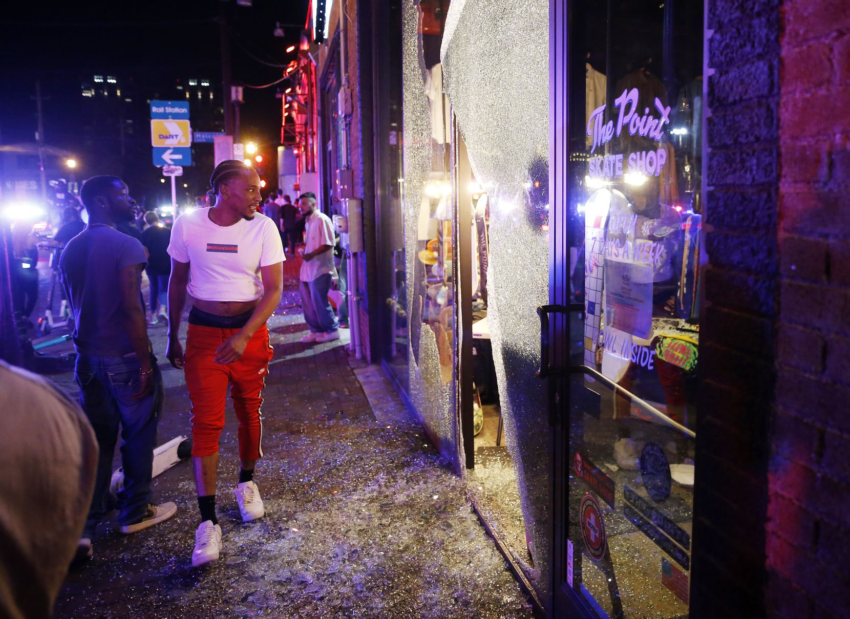 People look inside of the busted window of The Point Skate Shop along Main Street in Deep Ellum in downtown Dallas, on Friday, May 29, 2020. George Floyd died in police custody in Minneapolis on May 25.