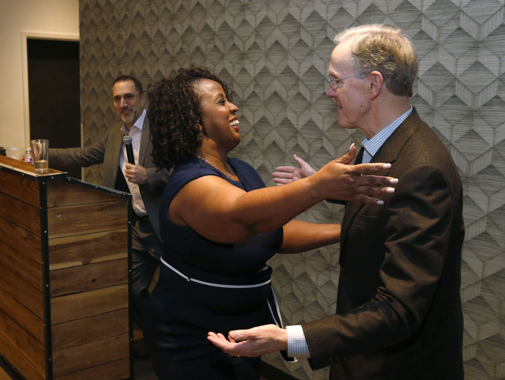 Leona Allen gives a hug to A. H. Belo Corp. CEO Robert Decherd after being announced as this year's winner of a civic journalism award bearing Decherd's name.