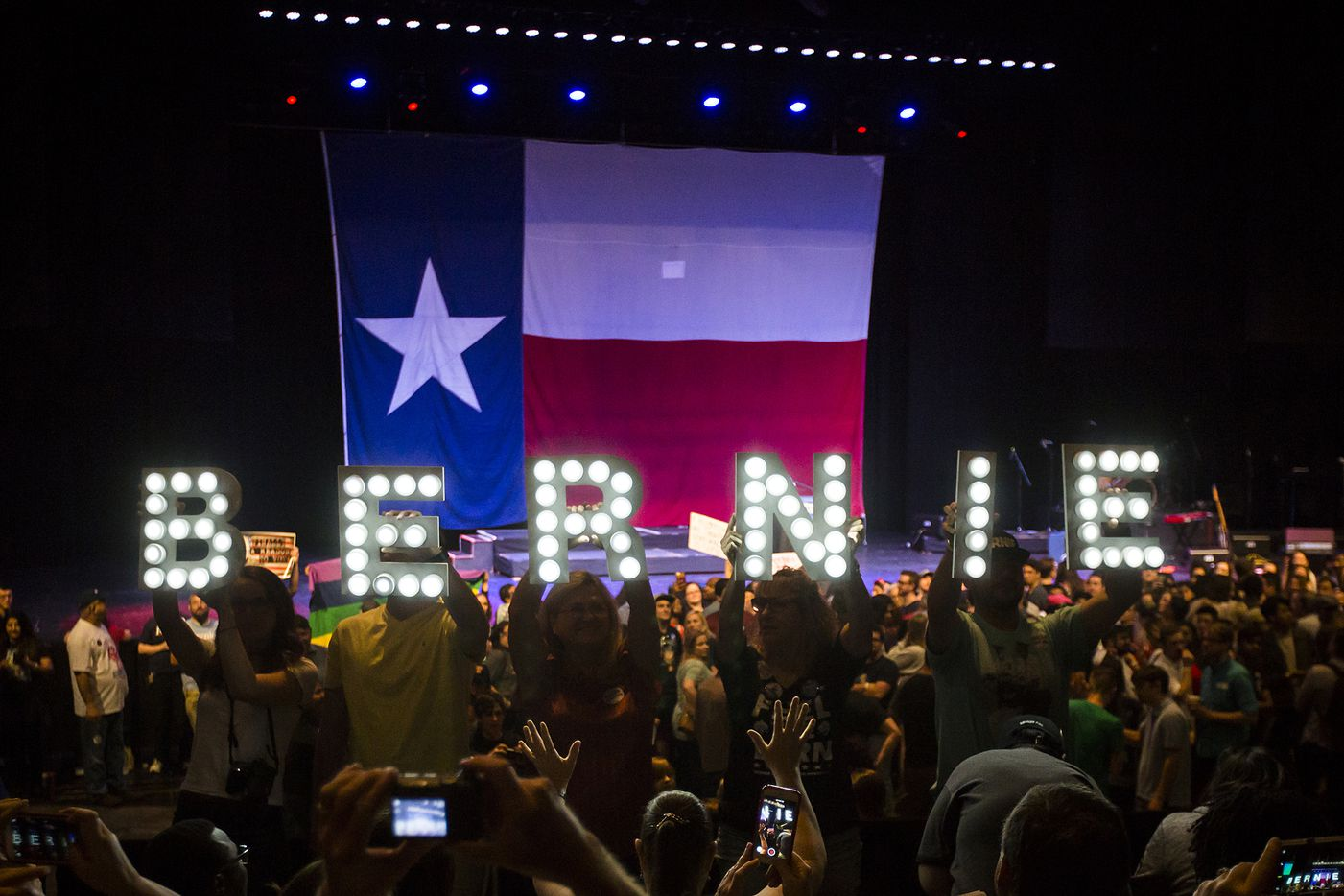 "Supporters hold signs while waiting for Vermont senator Bernie Sanders to take the stage for a rally at the Verizon Theater on Thursday, April 20, 2017, in Grand Prairie, Texas. Sanders, the runner-up in the 2016 Democratic contest for president, appeared in North Texas as part of a national tour urging Democrats to ""Come Together and Fight Back"" against the agenda of President Trump."