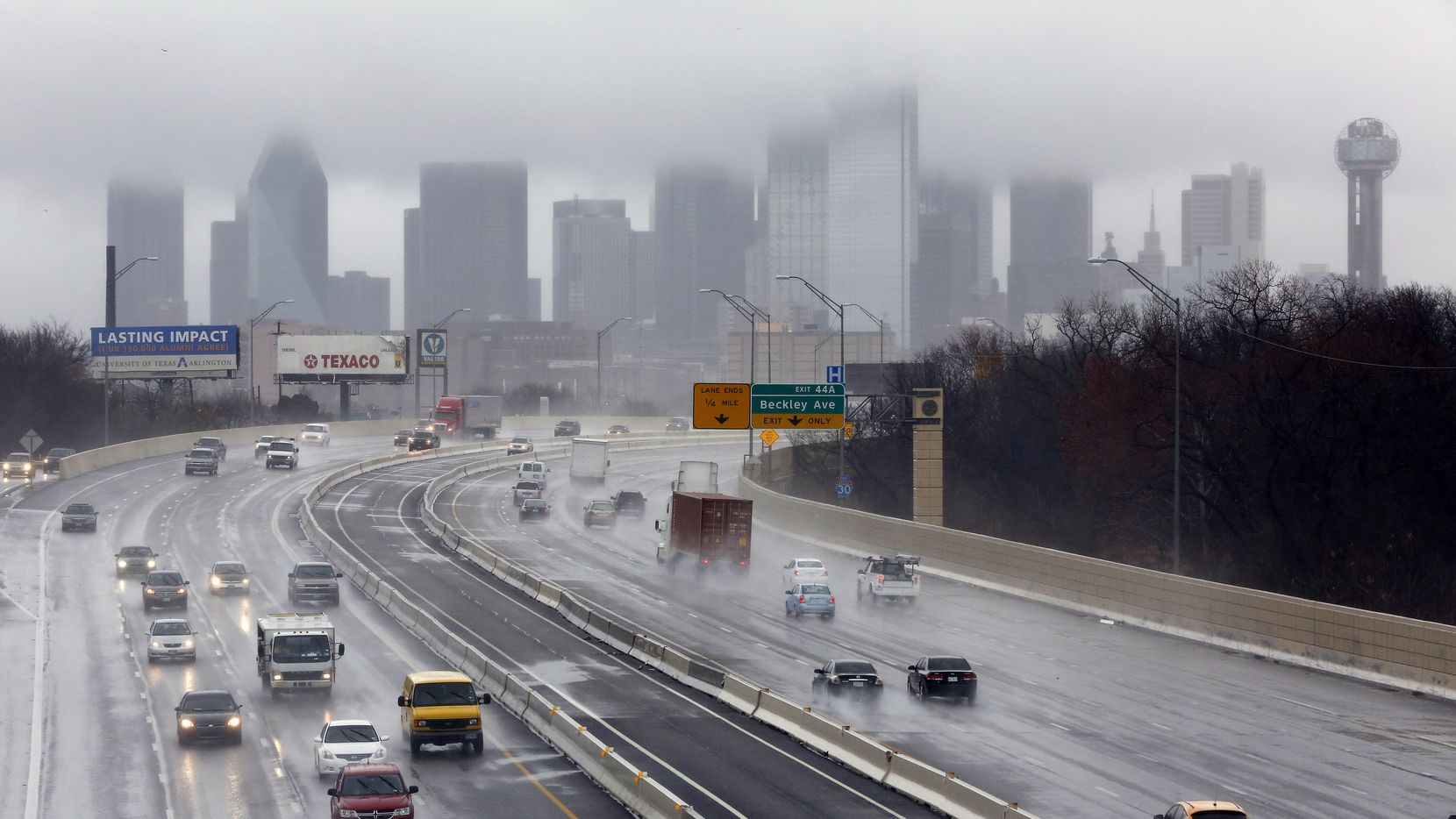 Motorists drive in the rain on Interstate I-35 south of downtown Dallas.