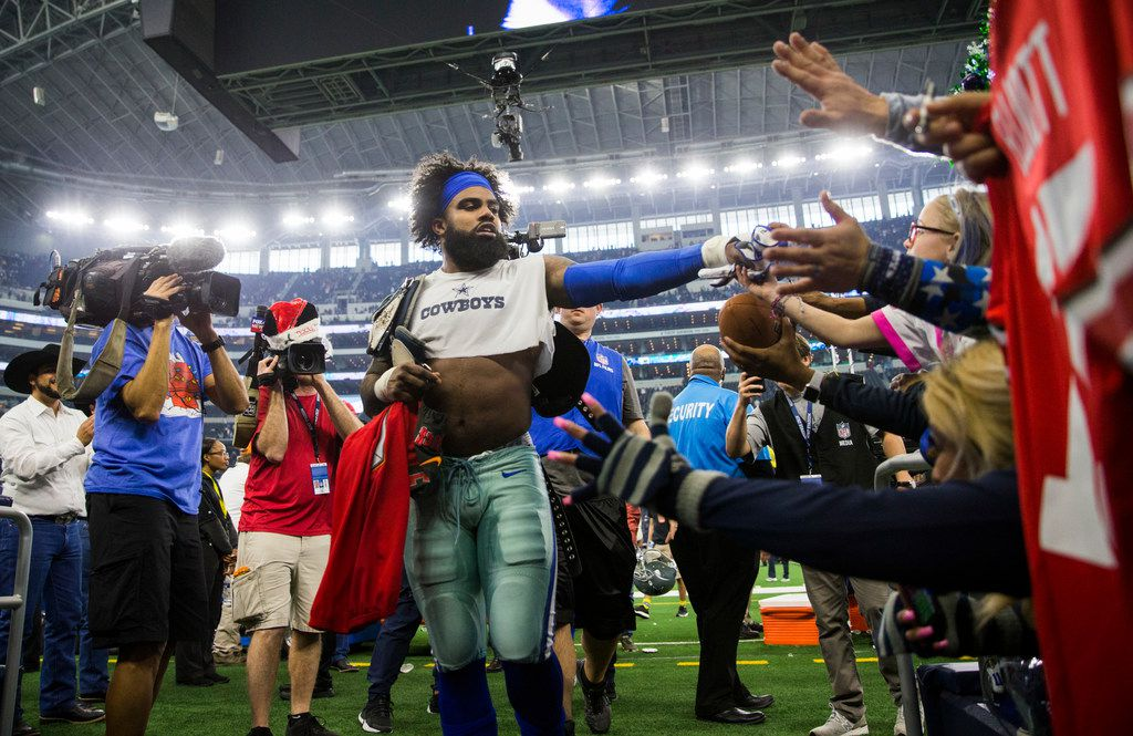 Dallas Cowboys running back Ezekiel Elliott (21) hands his gloves to a fan after an NFL game between the Dallas Cowboys and the Tampa Bay Buccaneers on Sunday, December 23, 2018 at AT&T Stadium in Arlington, Texas. Cowboys won 27-20. (Ashley Landis/The Dallas Morning News)