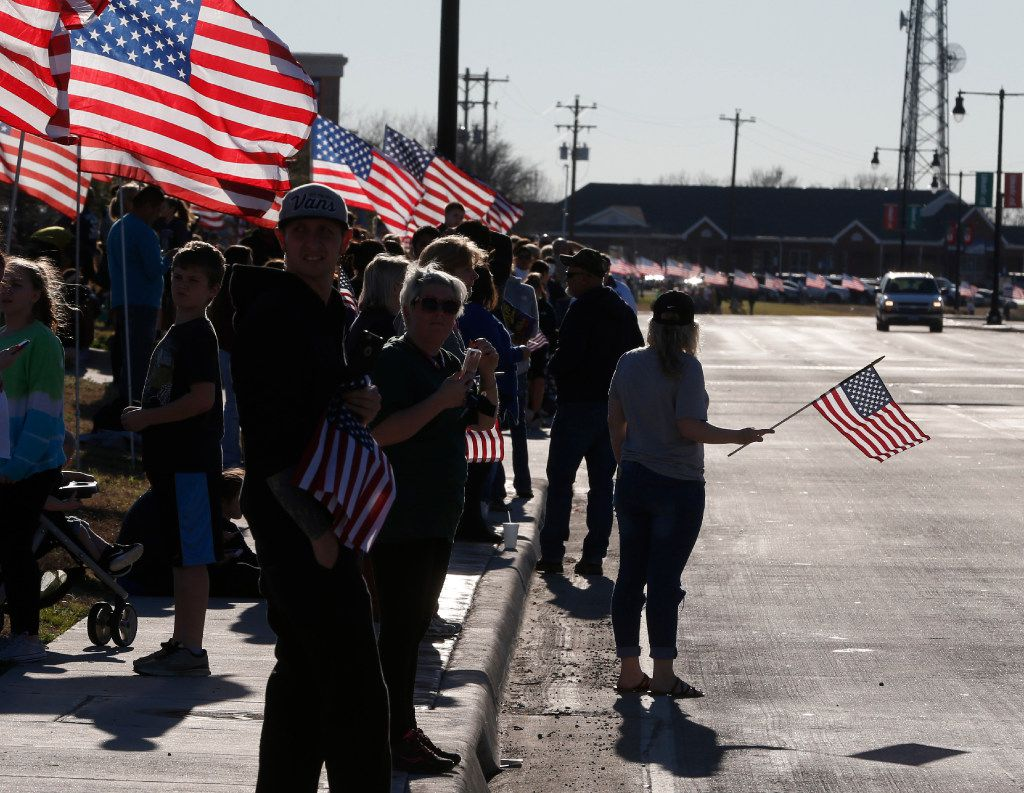 People wait with American flags before the procession route on Eldorado Pkwy for Det. Jerry Walker who was killed in the line of duty in Little Elm, Texas on January 23, 2017. (Nathan Hunsinger/The Dallas Morning News)