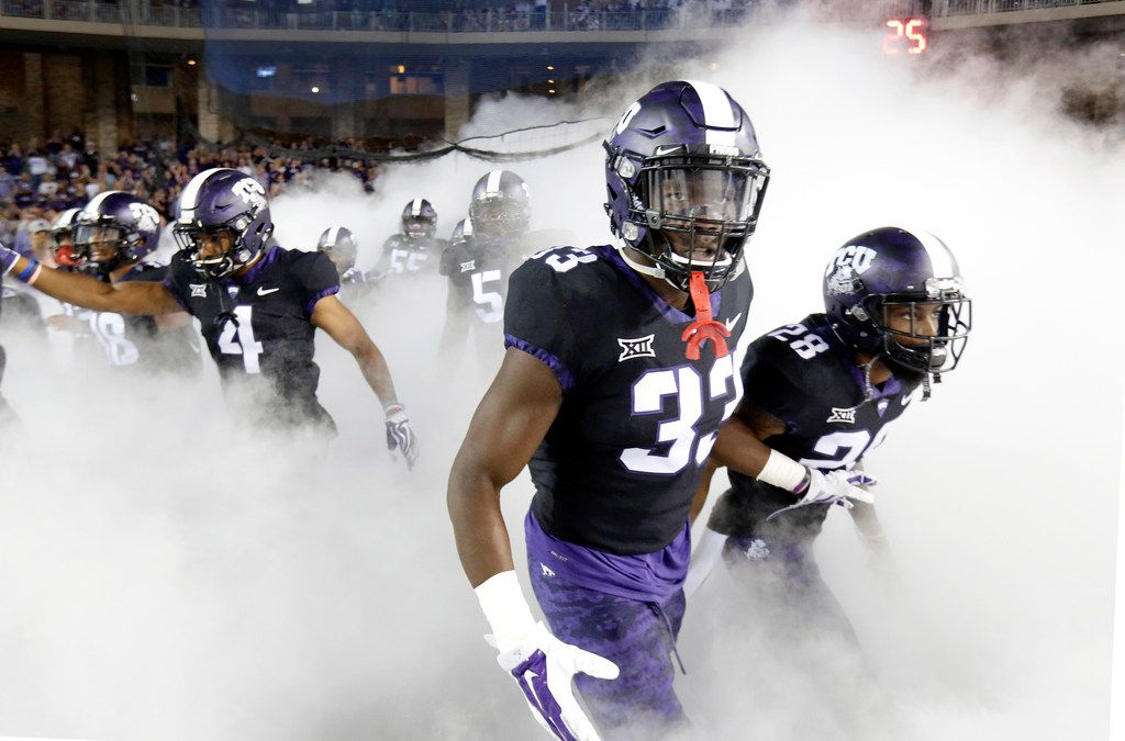 TCU Horned Frogs running back Sewo Olonilua (33) and his teammates race through the fog as they are introduced before the Kansas Jayhawks game at Amon G. Carter Stadium in Fort Worth, Texas, Saturday, October 21, 2017. (Tom Fox/The Dallas Morning News)