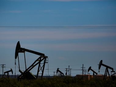 Oil pumpjacks line the horizon in the Permian Basin, where Pioneer Natural Resources is a major producer. There's pressure on the Irving-based company to cut spending and increase returns to shareholders.