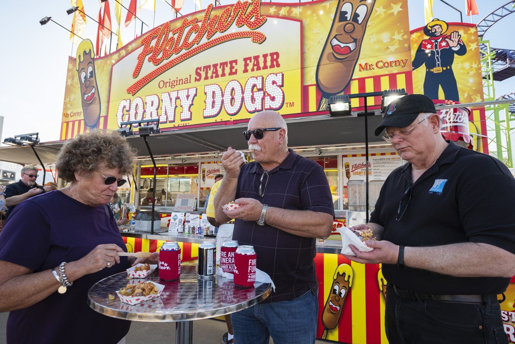 Perri Brackett, of Lewisville, left; Rick Murray, of Alvarado; and David McKenzie of Dallas taste test the new Fletcher's Dallas Hot Bird Dog the day before the State Fair of Texas opened in 2021.