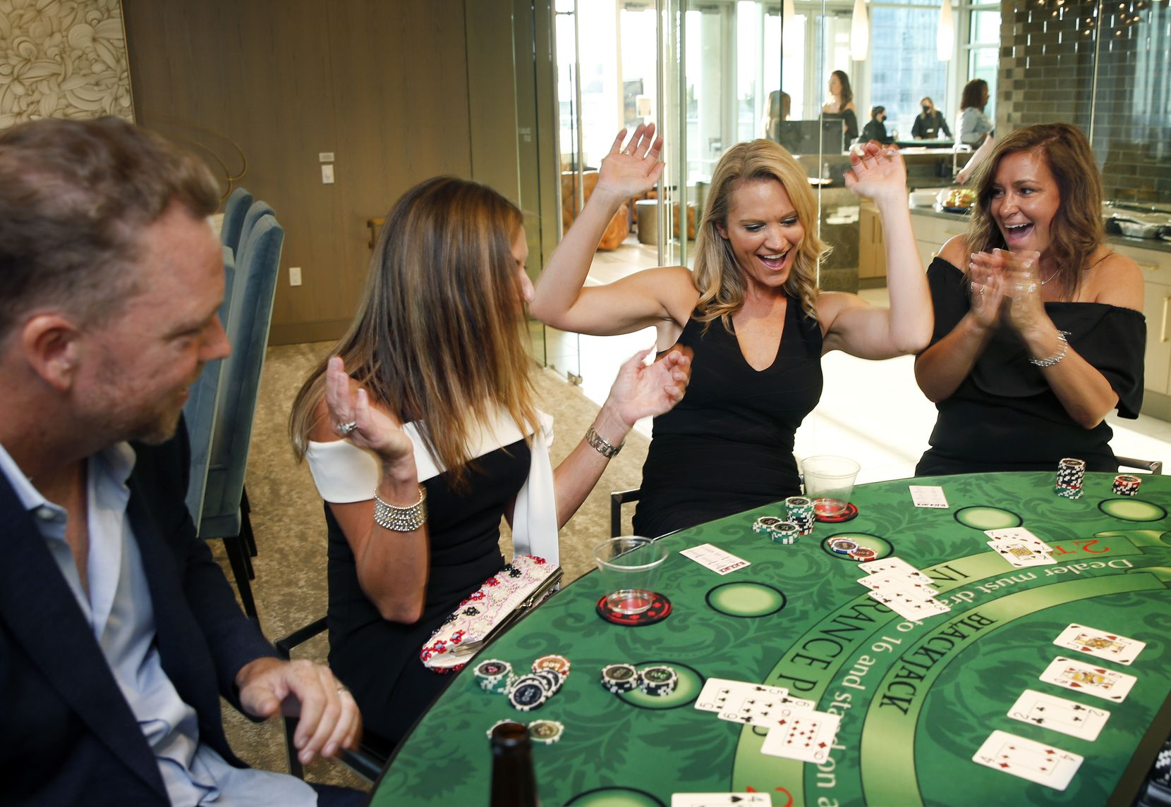 Monument Realty agents (from right) Angela Cunningham, Shannon Brownstein, Annmarie Eidman and owner Eddie Burns celebrate a winning blackjack hand on casino night.