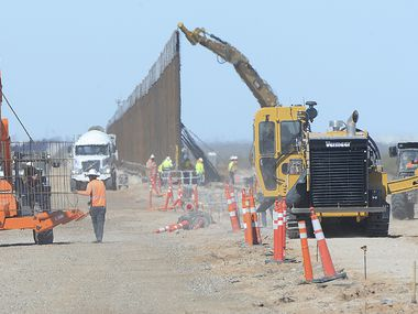 A construction worker (left) helps move a section of reenforcing grid into place while a trenching machine (right) digs a new footing and other construction workers assemble a 30-foot-high bollard style wall at a construction site south of Yuma, Ariz., near the border between the United States and Mexico.