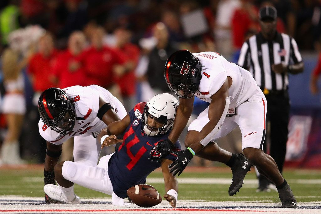 TUCSON, ARIZONA - SEPTEMBER 14:  Quarterback Khalil Tate #14 of the Arizona Wildcats fumbles the football as linebackers Riko Jeffers #6 and Jordyn Brooks #1 of the Texas Tech Red Raiders recover during the first half of the NCAAF game at Arizona Stadium on September 14, 2019 in Tucson, Arizona.