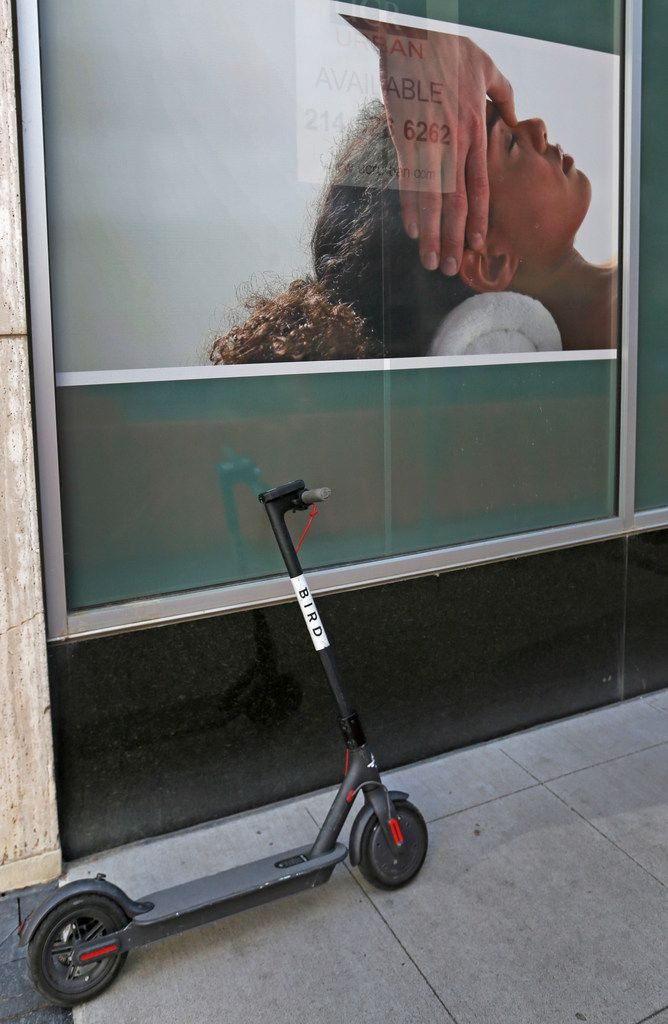 A rental scooter is parked alongside a business poster on Commerce Street in downtown Dallas.