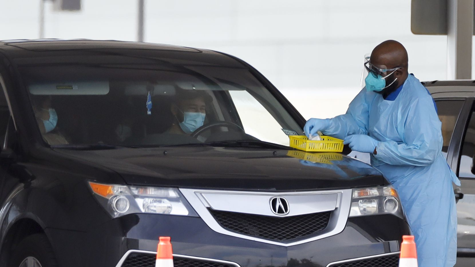 A health care worker prepares to collect a sample for a COVID-19 test at a drive-through testing site outside the Ellis Davis Field House in Dallas on Friday.