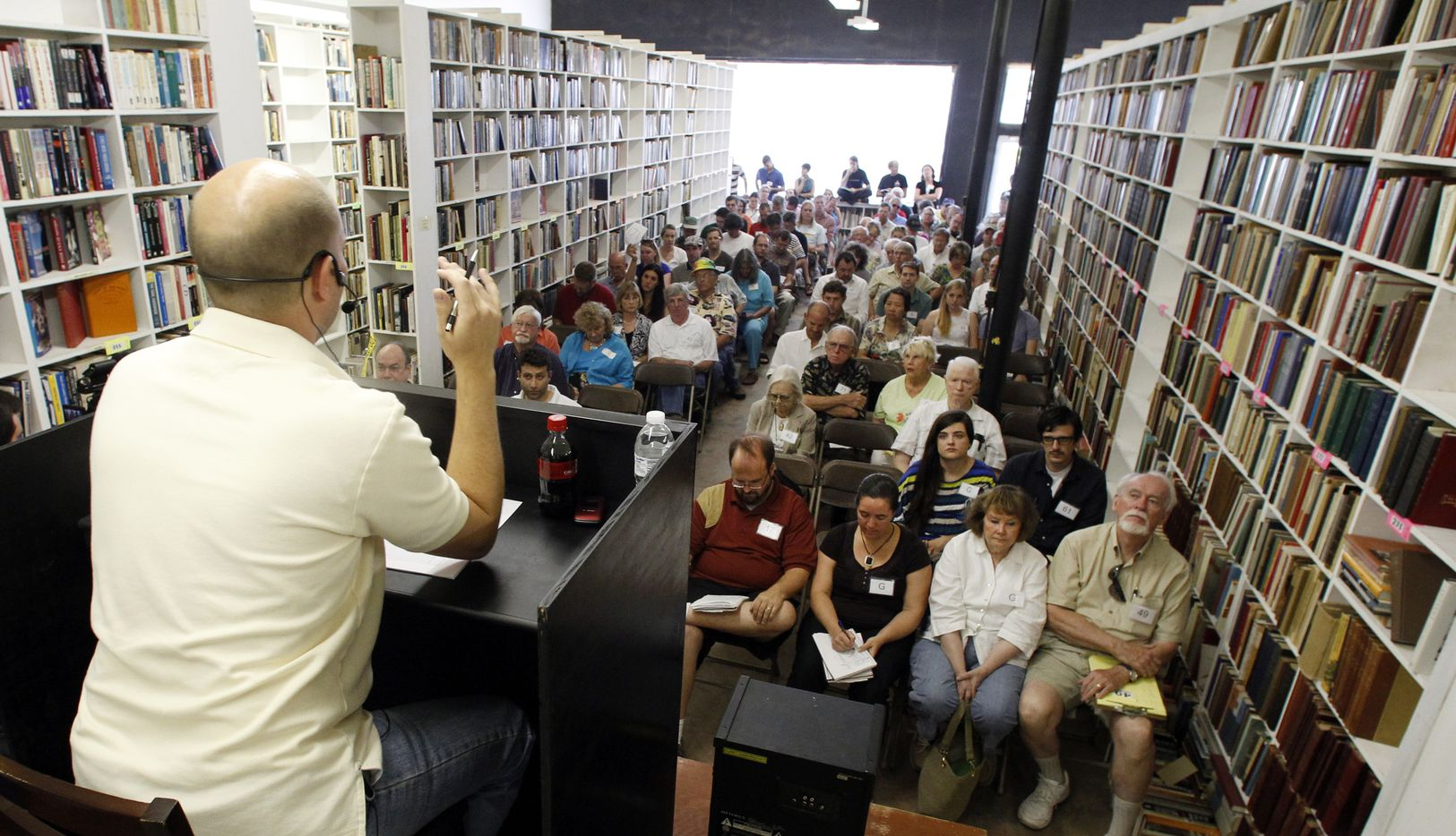 Michael Addison, left, auctions off Larry McMurtry's private collection of books in downtown Archer City in August, 2012.