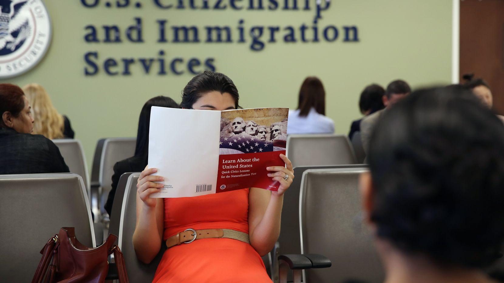 Una mujer espera en una oficina de USCIS mientras estudia su examen de ciudadanía.