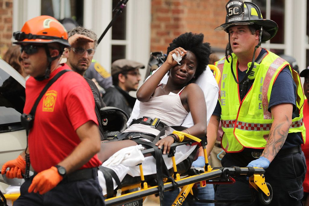 "CHARLOTTESVILLE, VA - AUGUST 12:  Rescue workers move victims on stretchers after car plowed through a crowd of counter-demonstrators marching through the downtown shopping district August 12, 2017 in Charlottesville, Virginia. The car plowed through the crowed following the shutdown of the ""Unite the Right"" rally by police after white nationalists, neo-Nazis and members of the ""alt-right"" and counter-protesters clashed near Lee Park, where a statue of Confederate General Robert E. Lee is slated to be removed.  (Photo by Chip Somodevilla/Getty Images) *** BESTPIX ***"