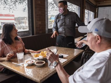 Waiter Francisco Licea, center, asks for the drink order of customers Teresa Torres, left, and Rafael Torres, right, as the couple sit in a covered patio area at Gloria's Latin Cuisine restaurant at the Bishop Arts District in Dallas, on the first day the mask mandate and occupancy limits are lifted, on Wednesday, March 10, 2021. Gloria's is not forcing their customers to wear a mask to enter the restaurant, but they have signage encouraging mask usage. All their employees must wear masks and they are operating at full capacity.