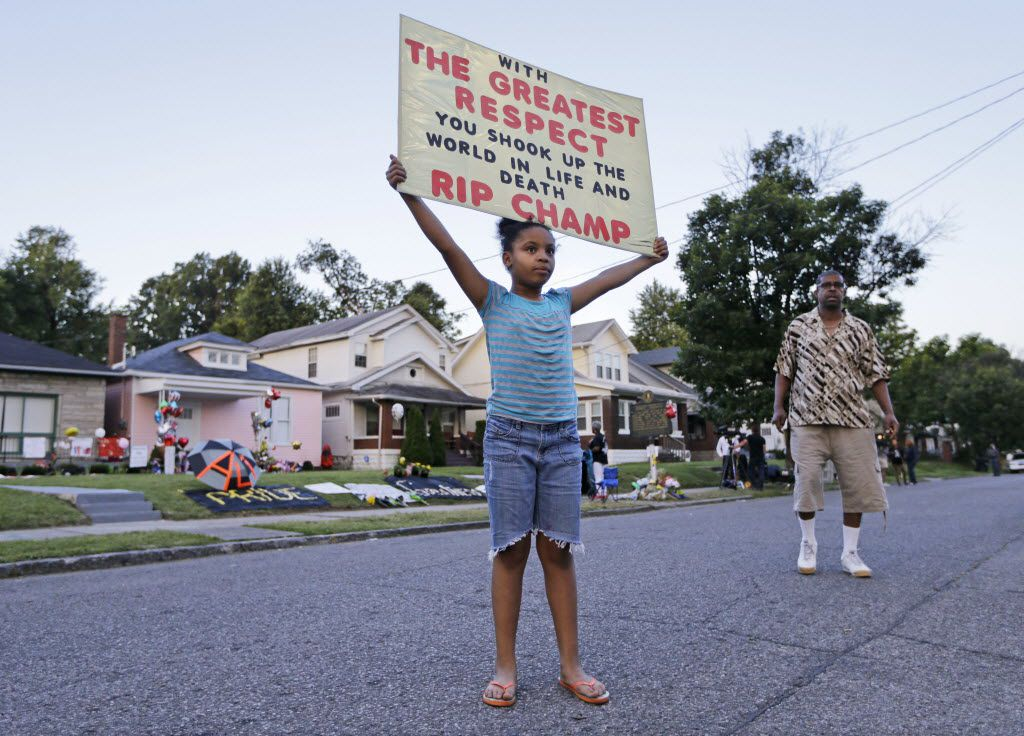 Akera Price-King, 9, carried a sign saluting Muhammad Ali on the street in front of Ali's boyhood home in June 2016 as Ali's funeral procession was set to pass by the house later in the day. (File Photo/The Associated Press)