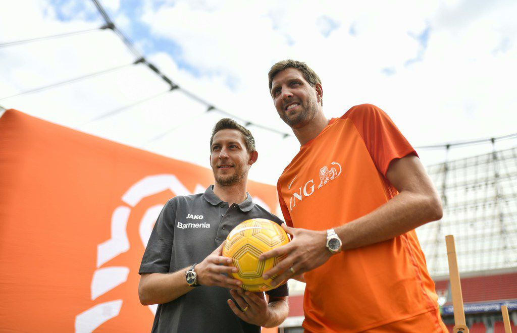 "German basketball legend Dirk Nowitzki (R) and former Bayer Leverkusen football player Stefan Kiessling pose with a ball during a news conference to promote the ""Champions for Charity"" event in Leverkusen, western Germany on Juli 3, 2019. - Nowitzki plays in the third edition of the charity event ""Champions for Charity"" taking place on July 21, 2019 in the BayArena stadium of Leverkusen against a team around Mick Schumacher, son of German Formula One legend Michael Schumacher, which will benefit the ""Dirk Nowitzki Foundation"" and the ""Keep Fighting"" initiative of the Schumacher family. (Photo by Ina FASSBENDER / AFP)INA FASSBENDER/AFP/Getty Images"
