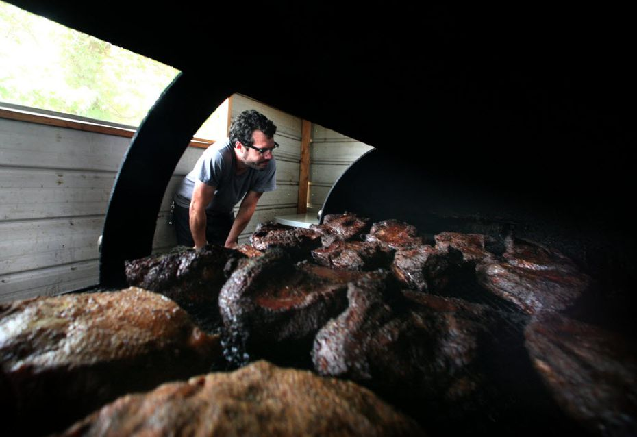 Aaron Franklin of Franklin Barbecue peeks inside his pit. He does this a lot, but he's a pro. Don't do it too much or your briskets will never cook.