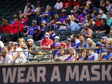Signs encourage fans to wear face coverings during a game between the Texas Rangers and the Baltimore Orioles at Globe Life Field on Sunday, April 18, 2021.