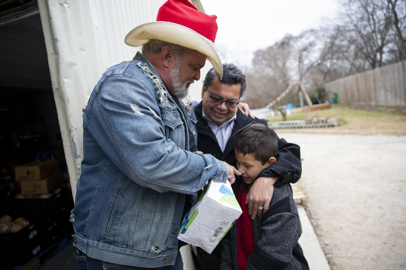 Leon Birdd (left) teased Marcelino Romero, 8, as he and Edgar Hernandez with Templo Cristiano Agape came by to load up from the Birdds' food pantry in Mesquite on Dec. 20, 2019. Local faith leaders used the donated food to help feed their communities.