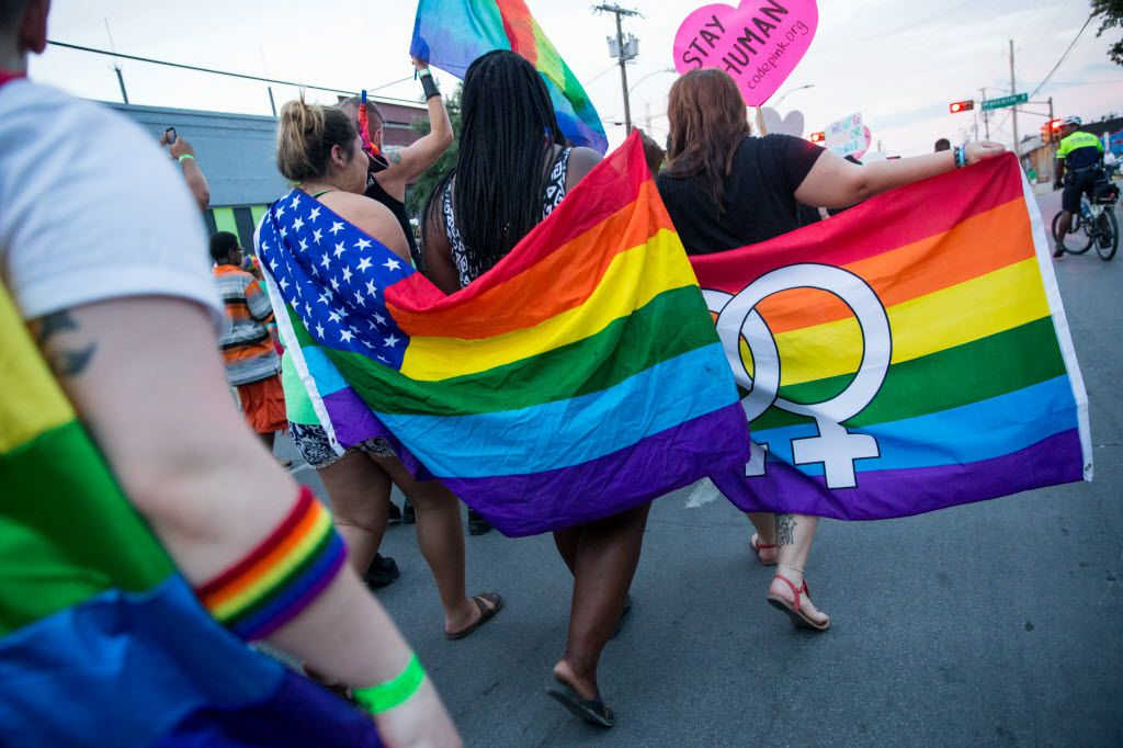Attendees of a 2016 march walk though Deep Ellum carrying rainbow flags in this file photo. (Ting Shen/The Dallas Morning News)