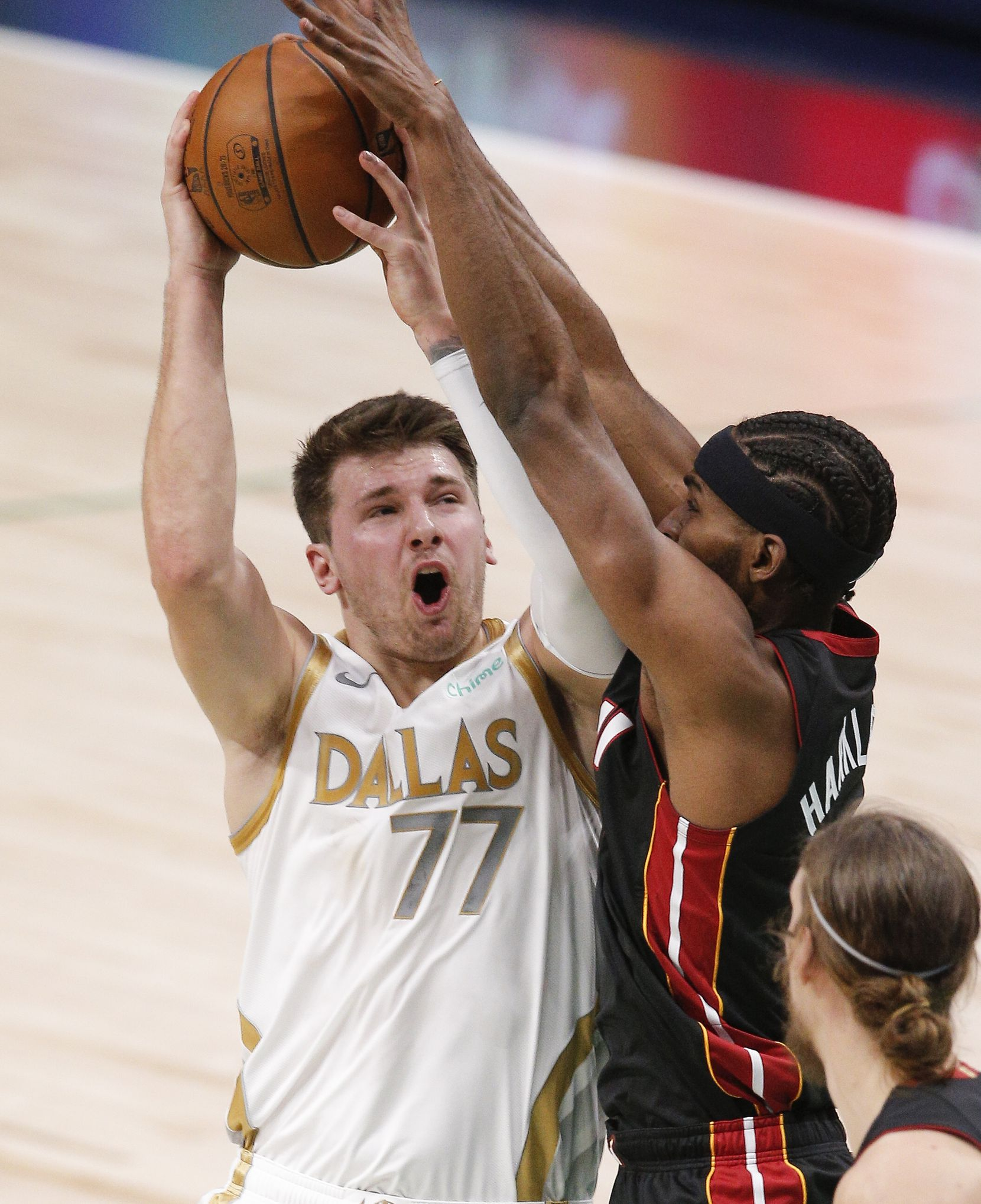 Dallas Mavericks guard Luka Doncic (77) attempts a shot as Miami Heat forward Maurice Harkless (8) defends during the first half of an NBA basketball game, Friday, January 1, 2021. (Brandon Wade/Special Contributor)
