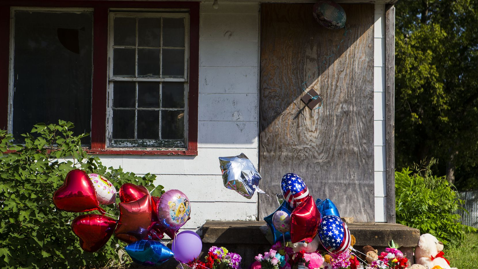 Memorial balloons and flowers wave in the wind at a home in the 2200 block of East Kiest Boulevard where a missing Lancaster teenager and a man were found dead early Sunday. (Ryan Michalesko/Staff Photographer)