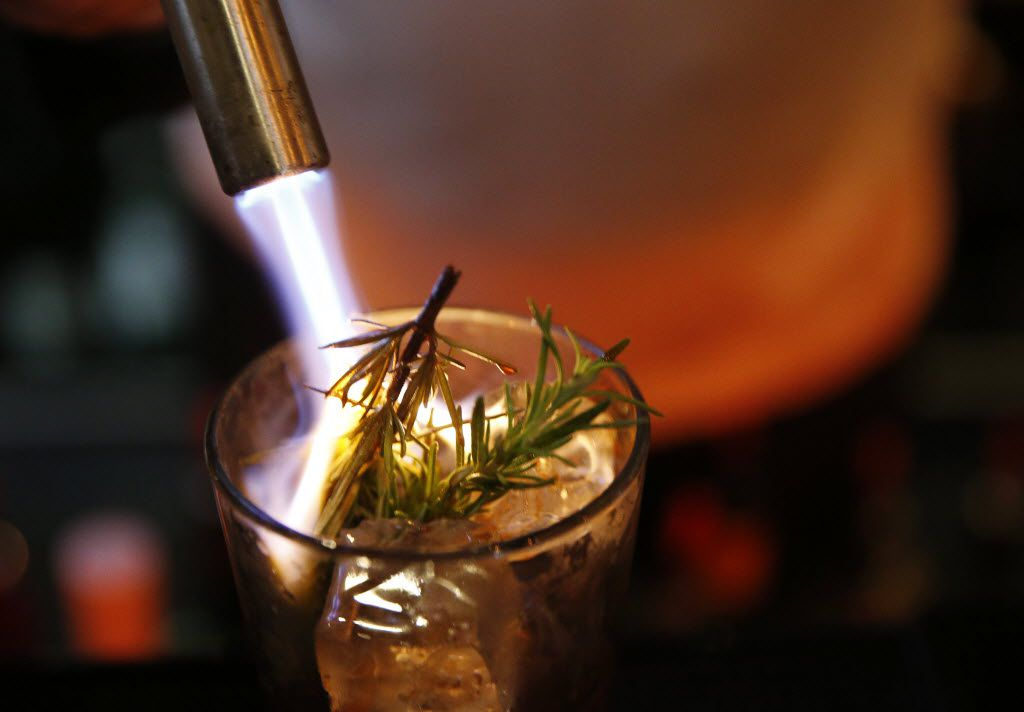 """Co-founded Brian McCullough burns rosemary while preparing the cocktail called """"Gringo in a Pine Box"""" behind the bar inside The Standard Pour dining room in Dallas Wednesday May 27, 2015."""