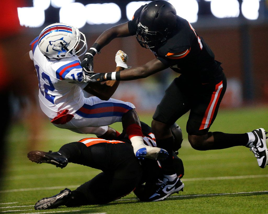 Duncanville running back Suavevion Persley (12) is tackled by Lancaster defensive back Kahn Rollerson (20, top) and linebacker Kourtney Washington (28, bottom) during the first quarter at Beverly D. Humphrey Tiger Stadium in Lancaster Texas, Friday, August 30, 2019. (Tom Fox/The Dallas Morning News)