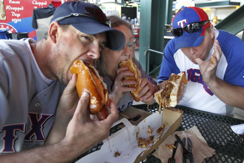 "Rangers fans Aaron McElroy, Sue Colson (mother) and brother Weston McElroy are the first to sample the ""Boomstick"" 24-inch hot dog before the Texas Rangers vs. the Chicago White Sox major league baseball season opener at Rangers Ballpark in Arlington on Friday,April 5, 2012. Man, that hot dog is big."