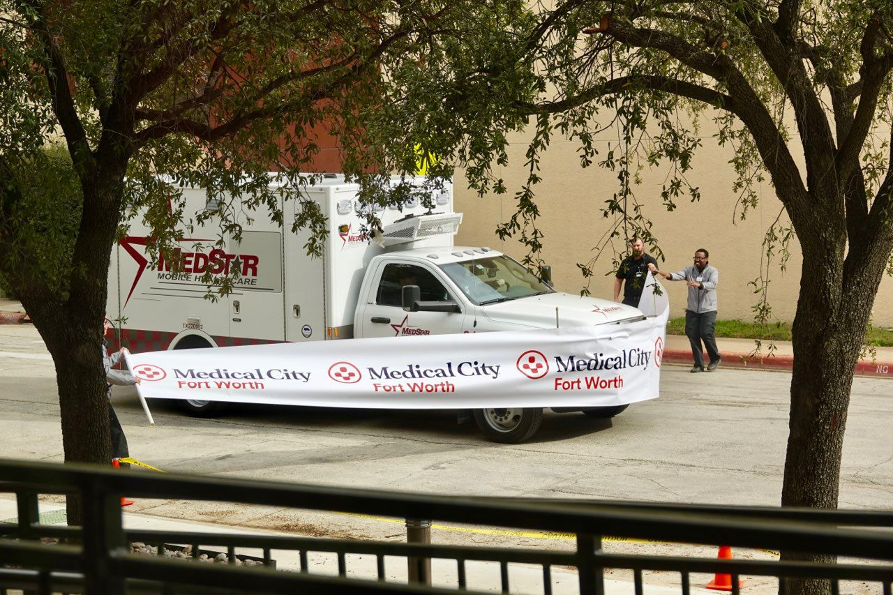 A MedStar emergency vehicle breaks through a giant ribbon to celebrate the opening of Medical City Fort Worth's new three-story tower that expands emergency services.