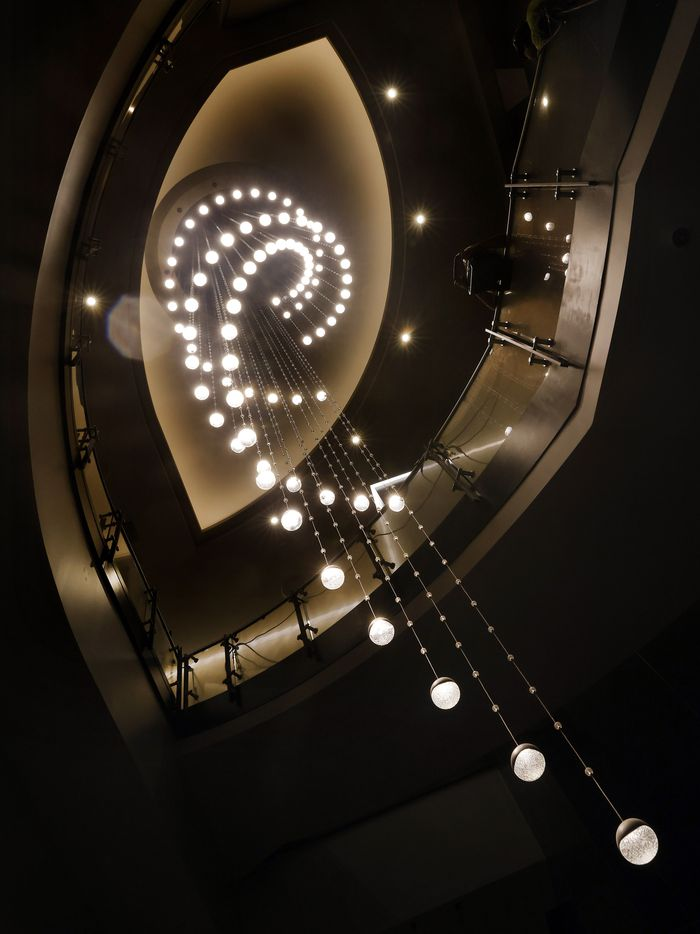 A three-story circular light fixture hangs alongside the grand staircase in the Sky Tower lobby.