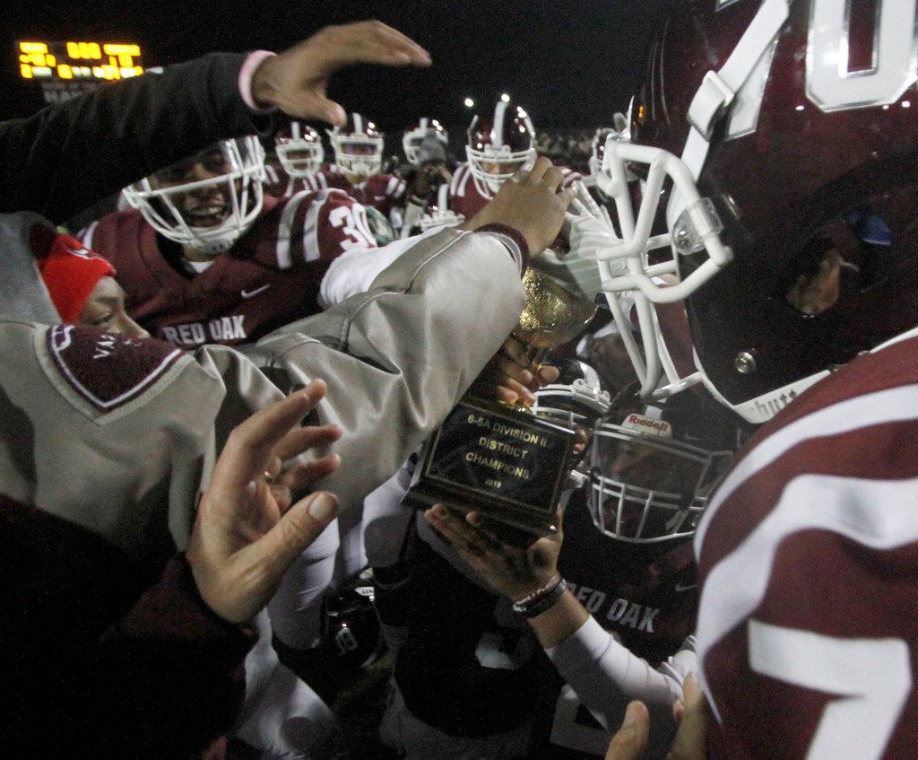 Held by Red Oak quarterback Joshua Ervin (2), the District 6-5A Division ll trophy became the center of attention at midfield as Hawks players celebrate following their 48-13 victory over Seagoville. The two teams played District 6-5A Division ll football game at Billy Goodloe Stadium in Red Oak on November 7, 2019. (Steve Hamm/ Special Contributor)