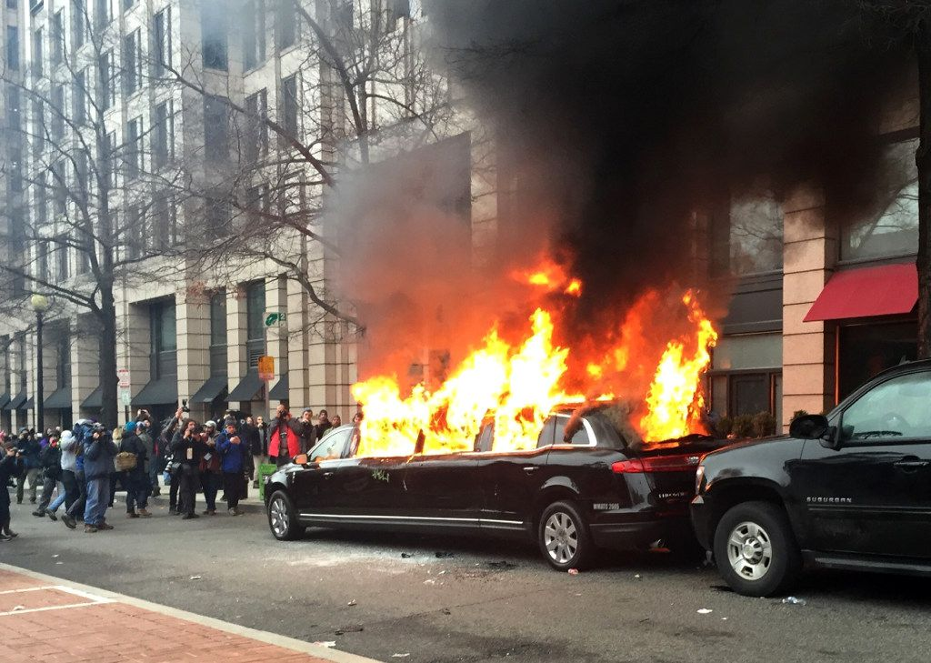 Protesters set a parked limousine on fire in downtown Washington on Friday during the inauguration of President Donald Trump. Protesters registered their rage against the new president Friday in a chaotic confrontation with police who used pepper spray and stun grenades in a melee just blocks from Donald Trump's inaugural parade route. Scores were arrested for trashing property and attacking officers. (Juliet Linderman/The Associated Press)
