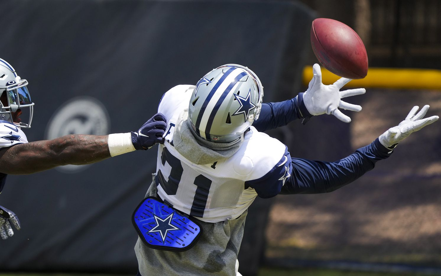Dallas Cowboys running back Ezekiel Elliott (21) makes a catch as linebacker Keanu Neal (42) defends during a practice at training camp on Wednesday, July 28, 2021, in Oxnard, Calif.