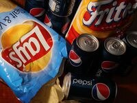 A bag of chips maufactured by PepsiCo's Frito-Lay brand and cans of its Pepsi soda.
