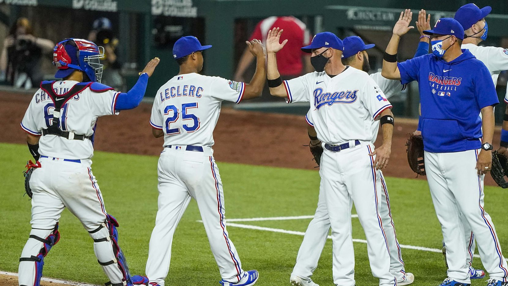 Texas Rangers pitcher Jose Leclerc bumps forearms with manager Chris Woodward as they celebrate after a 1-0 victory on opening day against the Colorado Rockies at Globe Life Field on Friday, July 24, 2020.