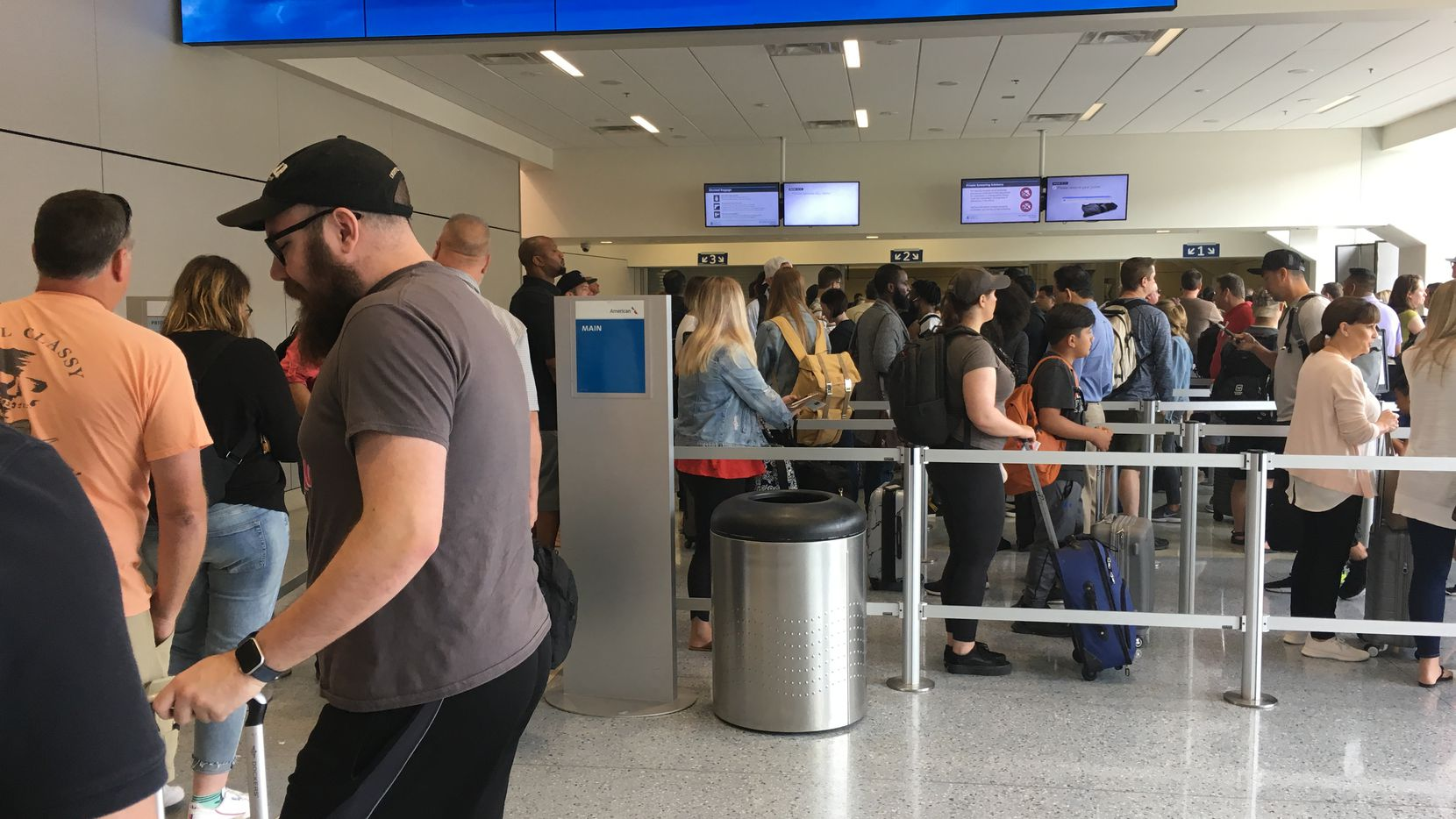 Travelers wait in crowded lines at DFW Airport Monday morning.