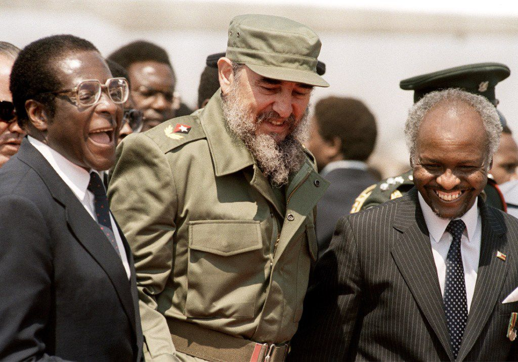 In this Aug. 31, 1986 file photo, Cuban President Fidel Castro (C), flanked by Zimbabwean President Robert Mugabe (L), arrives in Harare, for the 8th non-aligned summit in Zimbabwe.