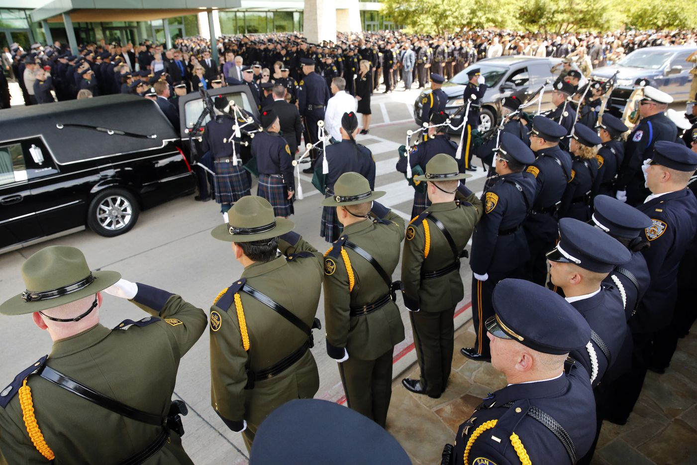 Border Patrol officers, front left, joined other officers as they salute fallen Dallas police officer Lorne Ahrens as the casket is placed in the hearse at Prestonwood Baptist Church in Plano, Wednesday, July 12, 2016.