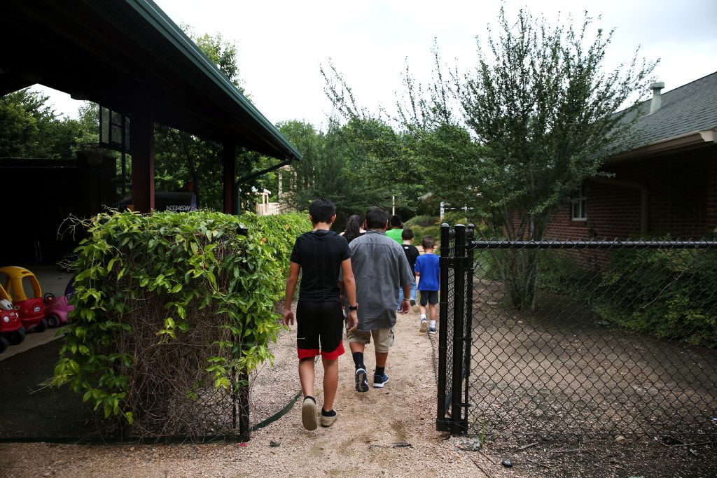 Boys in Child Protective Services' care walk through the courtyard at Jonathan's Place, which serves abused and neglected children, in Garland on June 30, 2017. (Rose Baca/The Dallas Morning News)