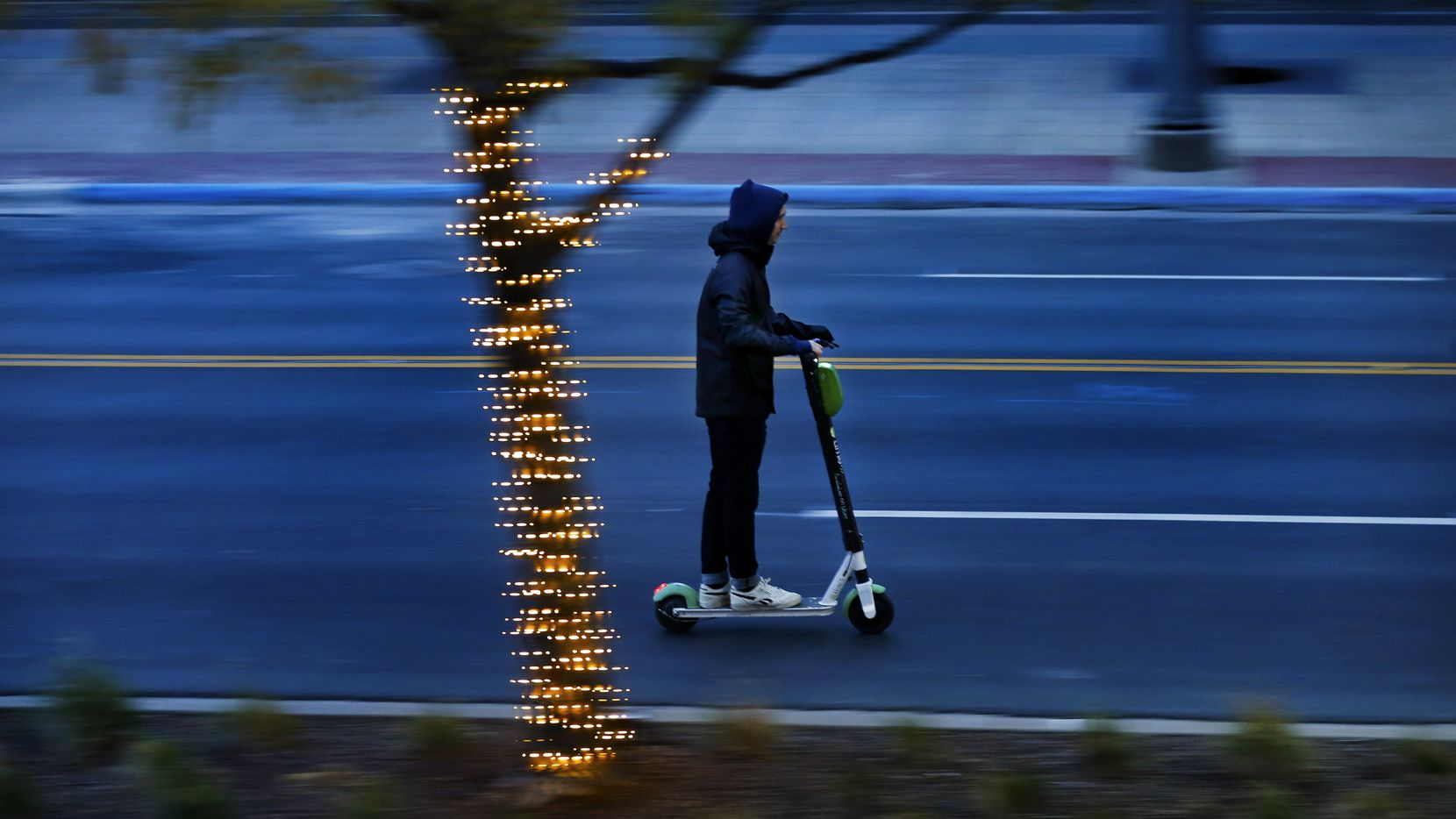 A bundled-up scooter rider breezed down Main Street in downtown Dallas as temperatures continued to fall Monday as a cold front moved into the area. The City Council is looking at some restrictions on scooters due to safety concerns.