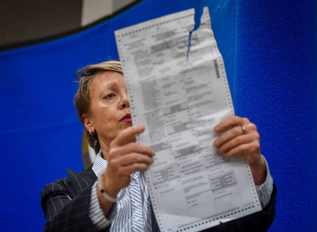 Judge Betsy Benson, canvassing Board Chair for Broward County Supervisor of Elections Office, shows ballots damaged by machines during the vote recount for three statewide races at the Broward County Supervisor of Elections headquarters on Nov. 14, 2018, in Lauderhill, Fla.