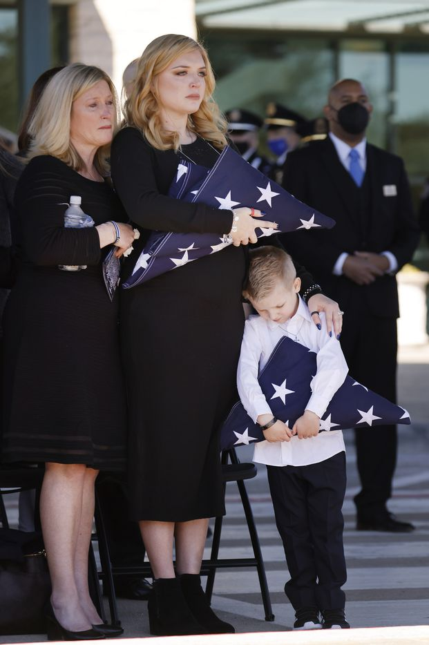 Nole Bergenske Penton (center) and her son Cashton grip folded U.S. flags given them by Dallas Police Chief Eddie Garcia following a funeral service for her husband Dallas Police officer Mitchell Penton at Prestonwood Baptist Church in Plano, Texas, Monday, February 22, 2021. Penton was killed, Saturday, Feb. 13, 2021, in a crash involving a drunk driving suspect. (Tom Fox/The Dallas Morning News)