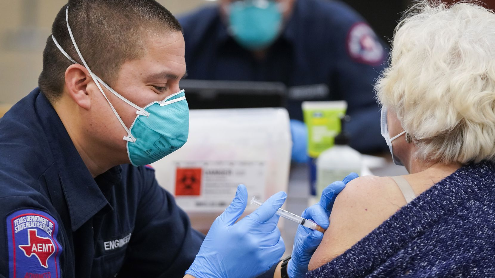 Arlington firefighter Jose Moreno administers the Moderna COVID-19 vaccine to a woman at the Esports Stadium Arlington & Expo Center on Tuesday, Jan. 5, 2021, in Arlington. (Smiley N. Pool/The Dallas Morning News)