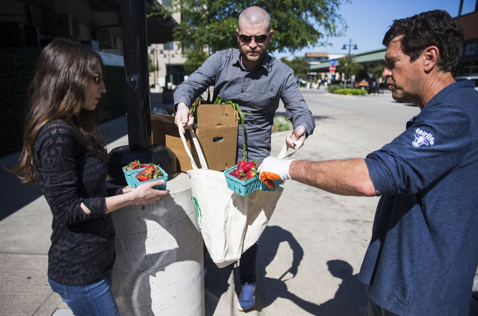 Farmer John Kilburn (right) of Comeback Creek Farm drops off a box of fruits and vegetables to customers Maude and David Hancock on Wednesday, April 15, 2020, at the Dallas Farmers Market in Dallas. (Ashley Landis/The Dallas Morning News)