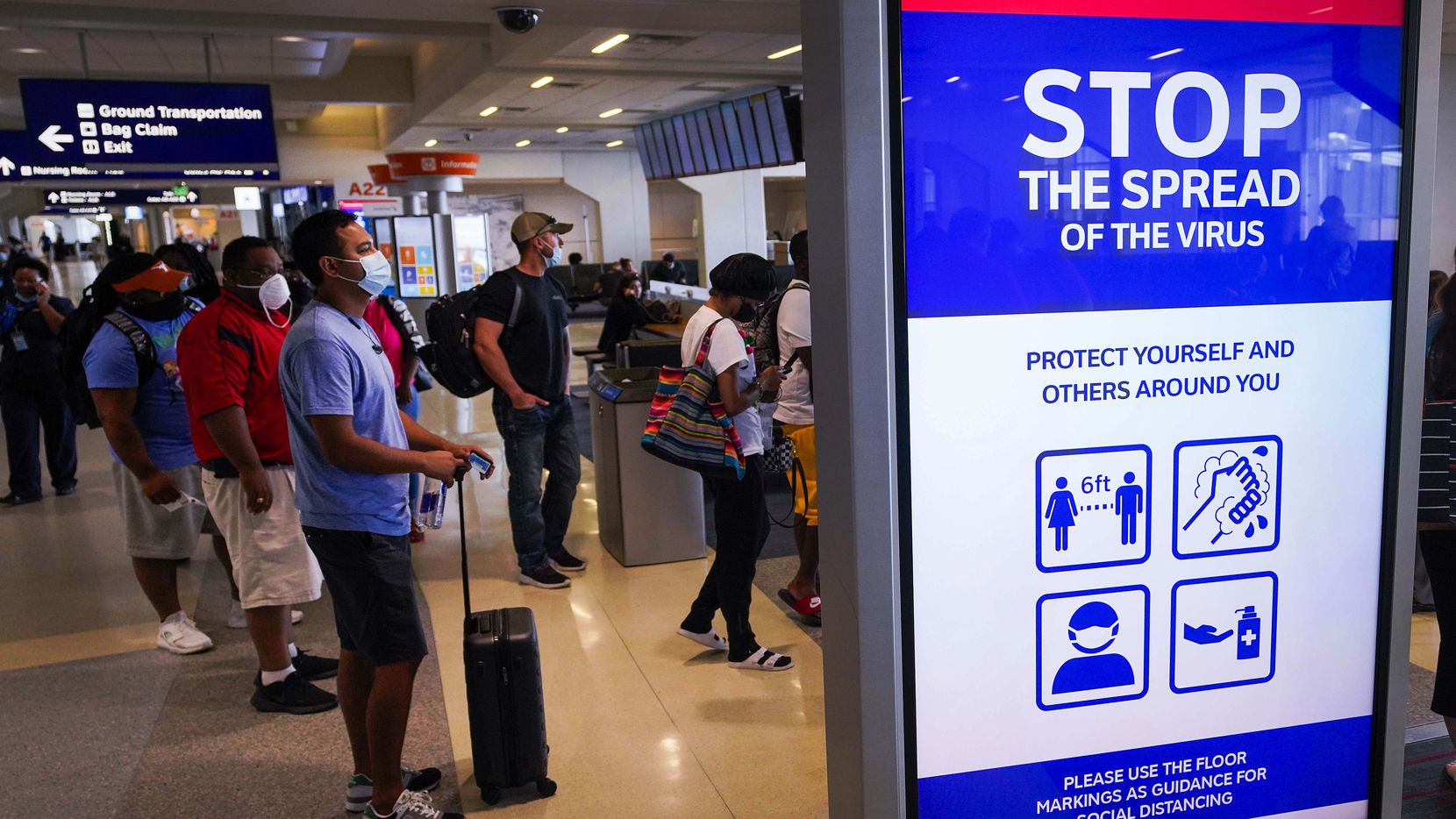 A message board displays a public health notice of precautions against the spread of COVID-19 as passengers wait to board an American Airlines flight at DFW International Airport Terminal A on Tuesday, June 30, 2020.