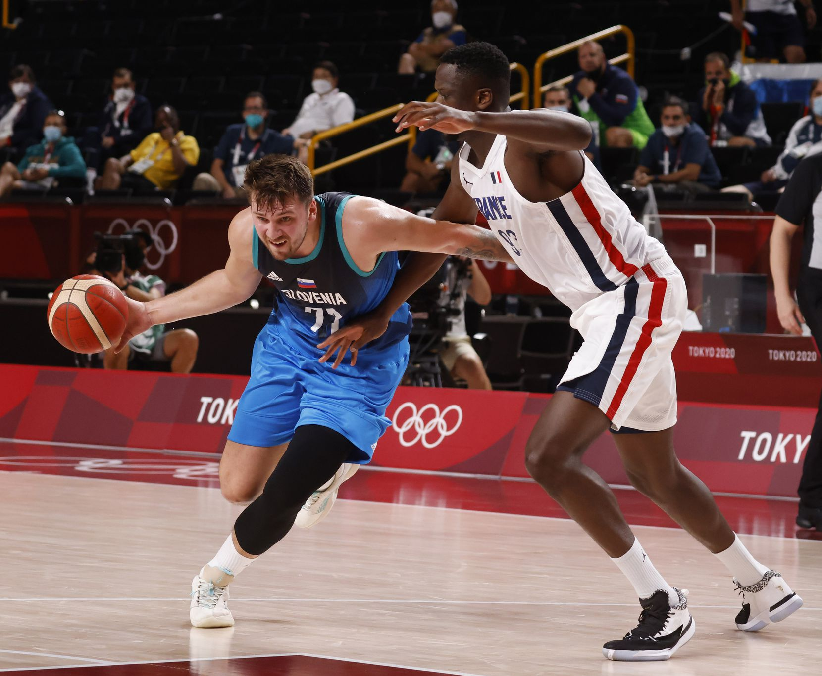 Slovenia's Luka Doncic (77) drives to the basket as he is defended by France's Moustapha Fall (93) during the first half of a men's basketball semifinal at the postponed 2020 Tokyo Olympics at Saitama Super Arena, on Thursday, August 5, 2021, in Saitama, Japan. (Vernon Bryant/The Dallas Morning News)