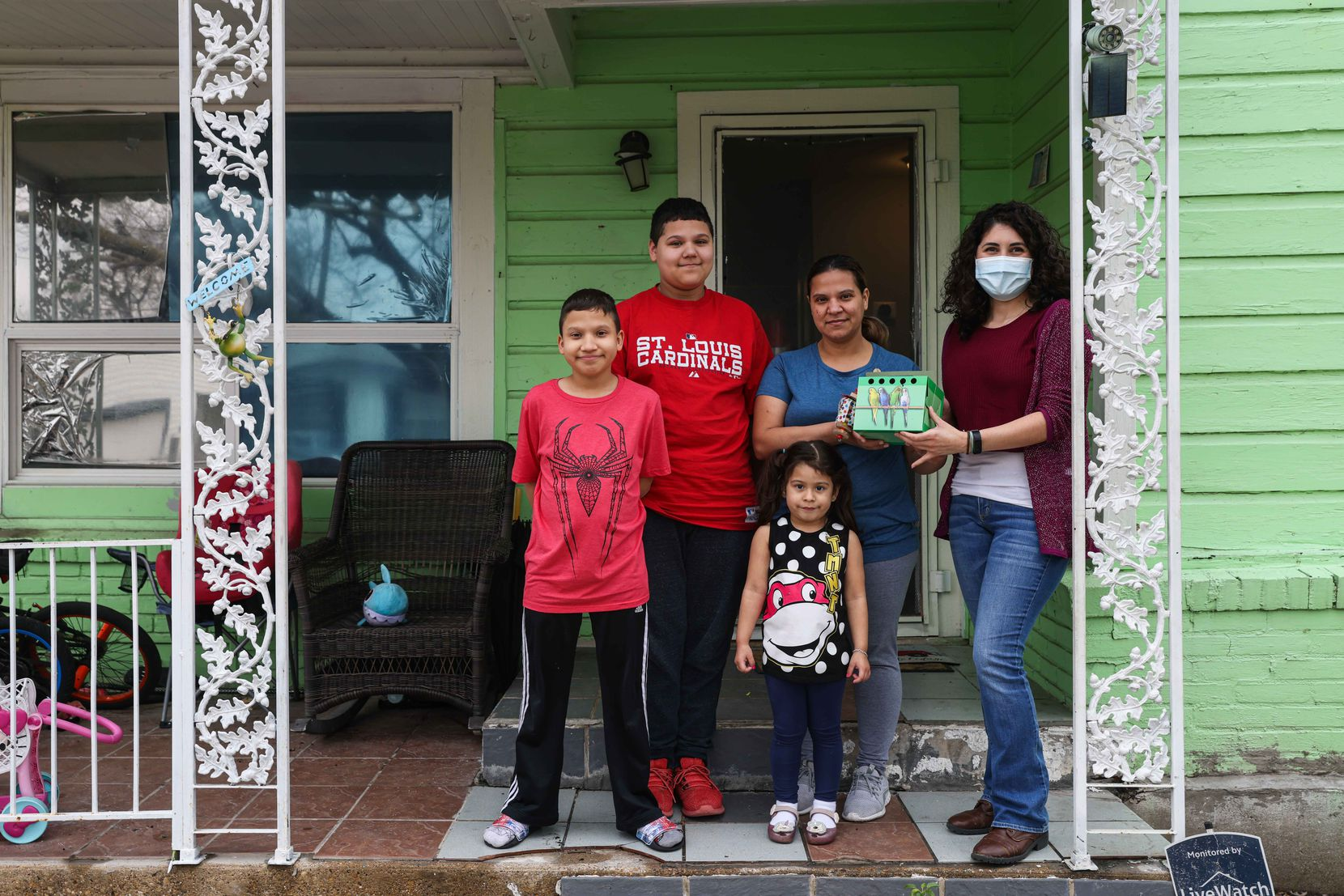 From left, Aaron Hall, Matthew Hall, Marleny Almendarez, Madelyne Hernandez and Allison Olivarez, pose together in front of Almendarez home with their new pet bird, a peach-faced Lovebird, in Dallas on Friday, February 26, 2021. They lost their pet bird, Little Rainbow, during the severe winter storm that hit Texas two weeks ago when he froze to death after the power went out in her house for days, bringing the temperature inside around 40 degrees Fahrenheit.